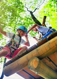 Little girl helping her brother on ropes course